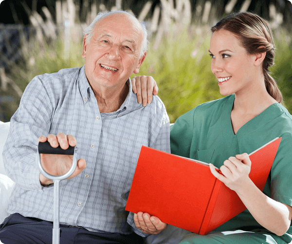 Caregiver assisting old man to read