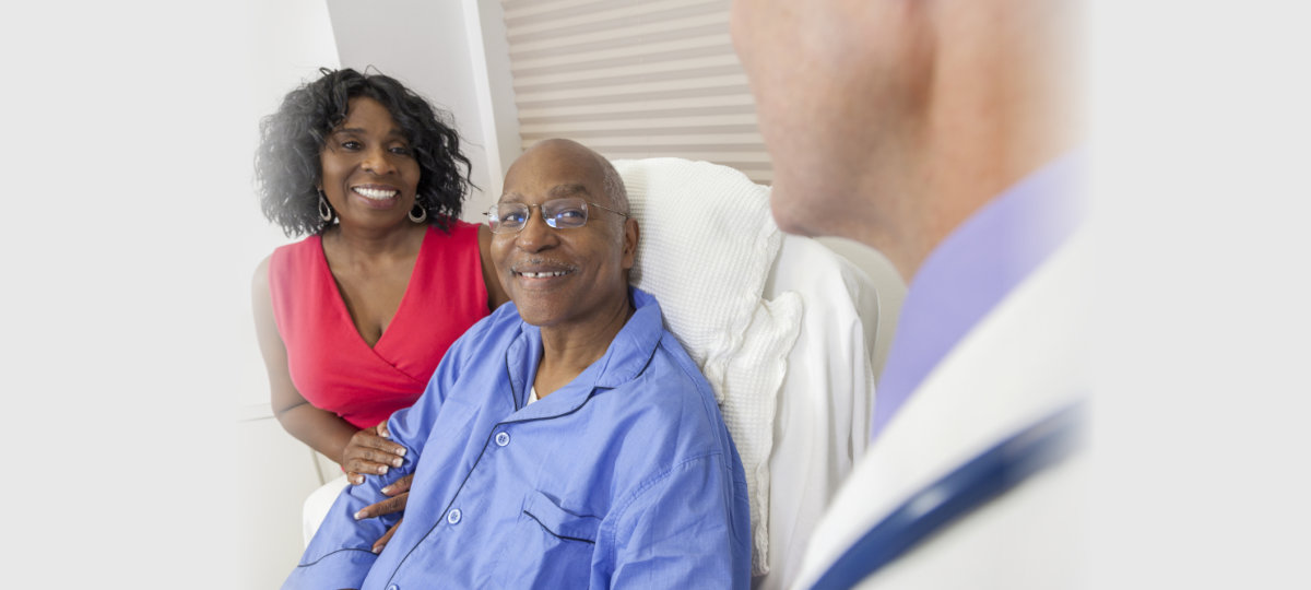 Happy senior African American men patient recovering in hospital bed with male doctor and wife