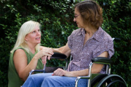 woman taking care of an elderly in a wheelchair